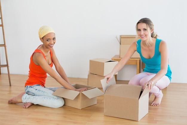 Amigos que desembrulham caixas em uma nova casa