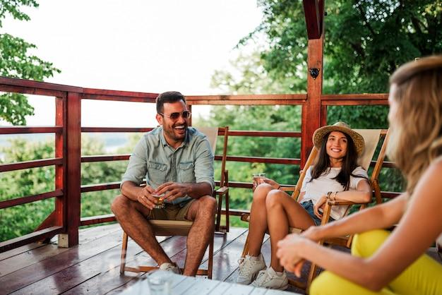 Amigos que relaxam no balcão de madeira na natureza.