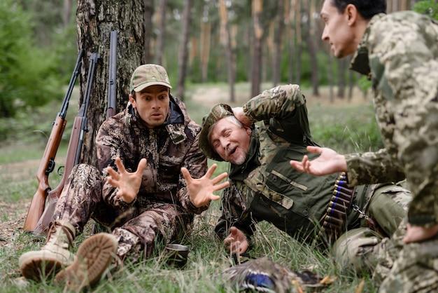 Amigos que riem de caçadores engraçados da história que descansam.