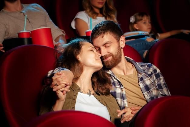 Amigos que sentam-se no filme do relógio do cinema que come a pipoca e a água bebendo.