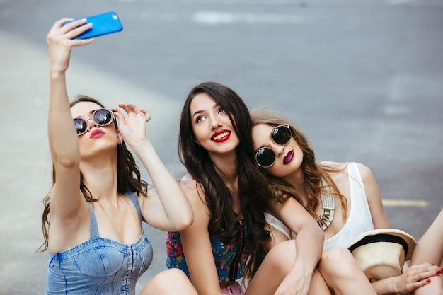 Amigos que tomam uma foto sentado no asfalto