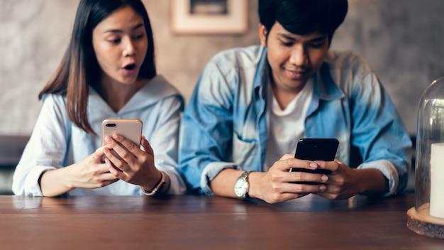 Amigos que usam o smartphone no café, durante o tempo de lazer.