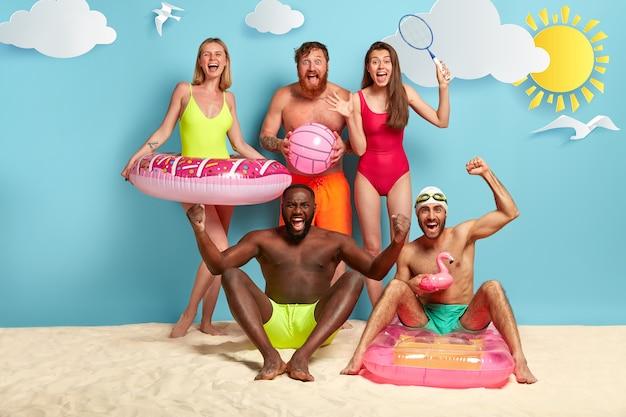 Amigos radiantes posando na praia