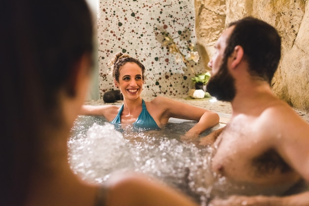 Amigos relaxantes e sorridentes na banheira jacuzzi no therme