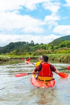 Amigos remando na rota em caiaque ou canoa nos pântanos do parque natural urdaibai, país basco