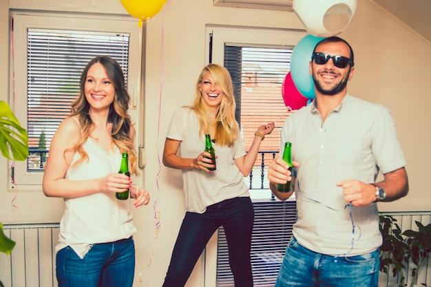 Amigos rir de festa com garrafa de cerveja