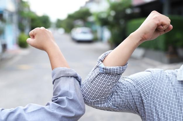 Amigos se cumprimentam com os cotovelos colidindo em vez de tocar as mãos.