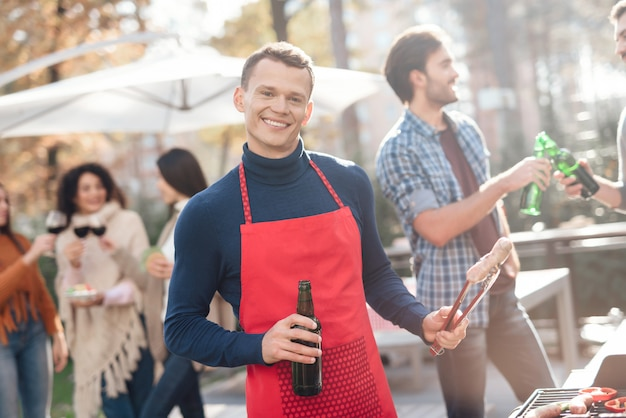 Amigos se divertem, cozinham comida, bebem álcool.