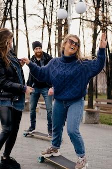 Amigos se divertindo andando de skate ao ar livre no parque