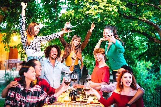 Amigos se divertindo ao ar livre brindando vinho tinto em uma festa no jardim