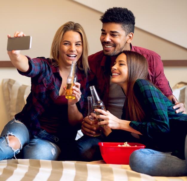 Amigos se divertindo, bebendo cerveja, tomando selfie.