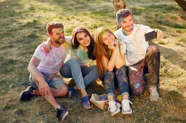 Amigos se divertindo em um parque com tintas holi