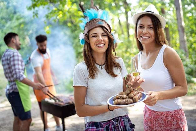 Amigos se divertindo na natureza fazendo churrasco
