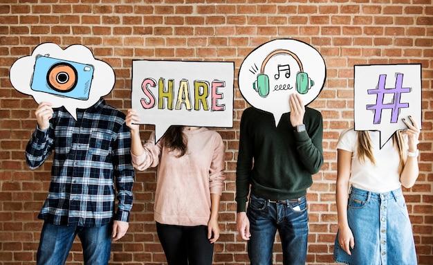 Amigos segurando balões de pensamento com ícones de conceito de mídia social