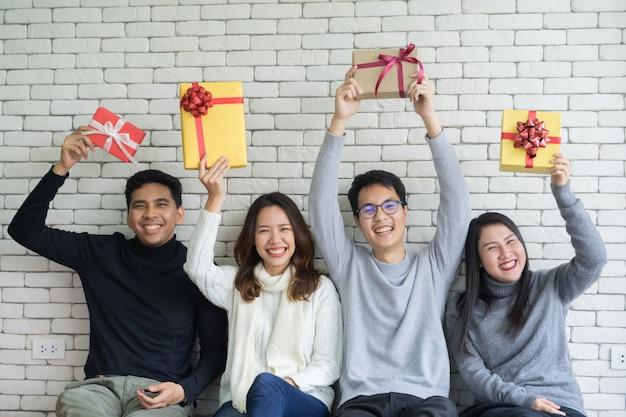 Amigos segurando caixas de presente em casa para o natal e feliz ano novo