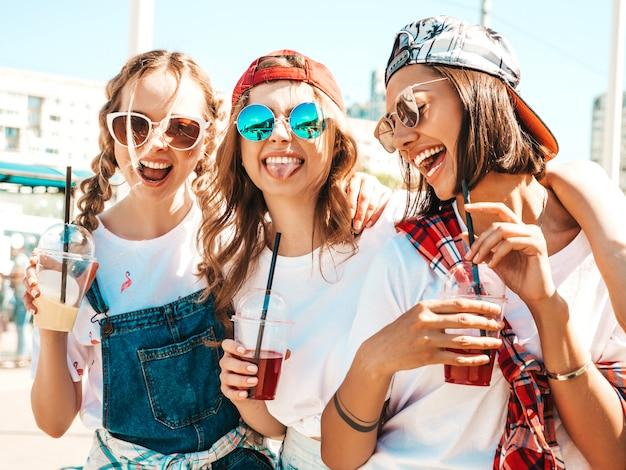 Amigos, segurando e bebendo smoothie de cocktail fresco bebem em copo de plástico com palha