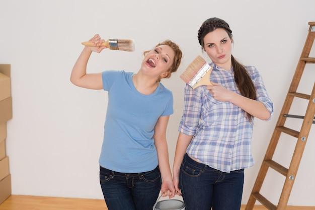 Amigos segurando pincéis e podem em uma nova casa