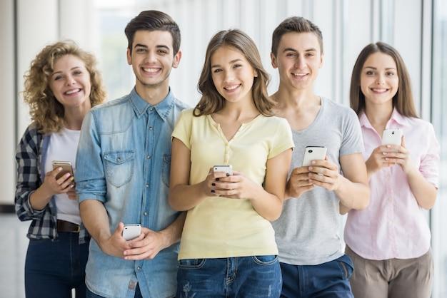Amigos, segurando, telefones, e, posar