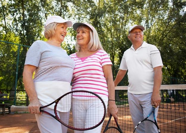 Amigos sêniores de tiro médio com raquete