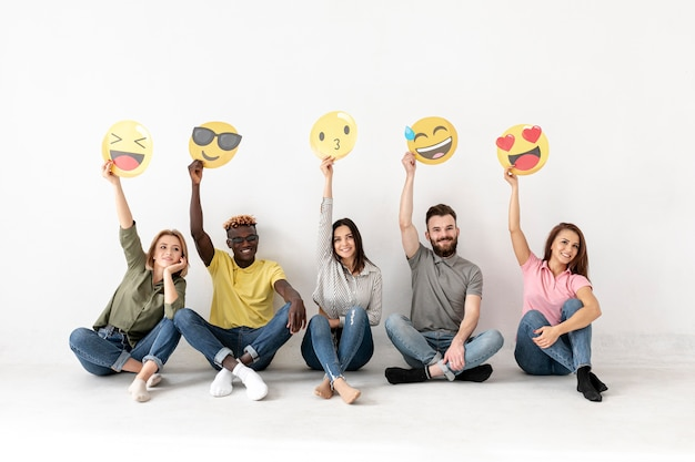 Amigos, sentada no chão e segurando emoji