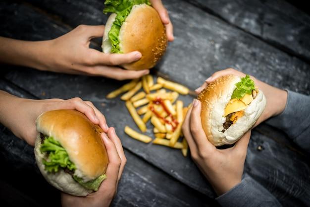 Amigos sentado e comendo hambúrguer