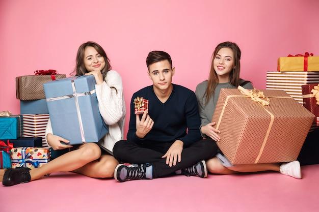 Amigos sentado entre presentes de natal. mulher segurando caixas grandes, cara pequena.