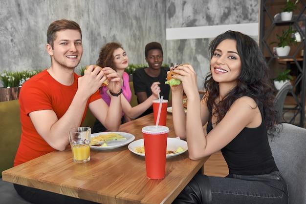 Amigos, sentado no café de fast-food, comendo hambúrgueres.