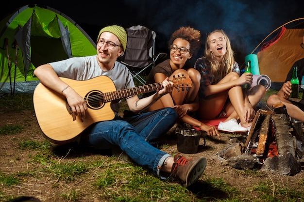 Amigos, sentado perto da fogueira, sorrindo, falando, descansando, tocando violão