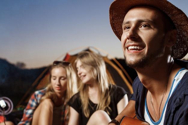 Amigos, sentado perto da fogueira, sorrindo, tocando violão camping grill marshmallow.