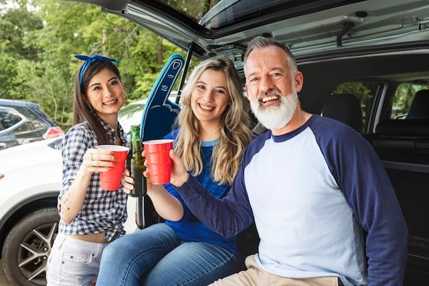 Amigos sentados e bebendo no porta-malas do carro em uma festa ao ar livre