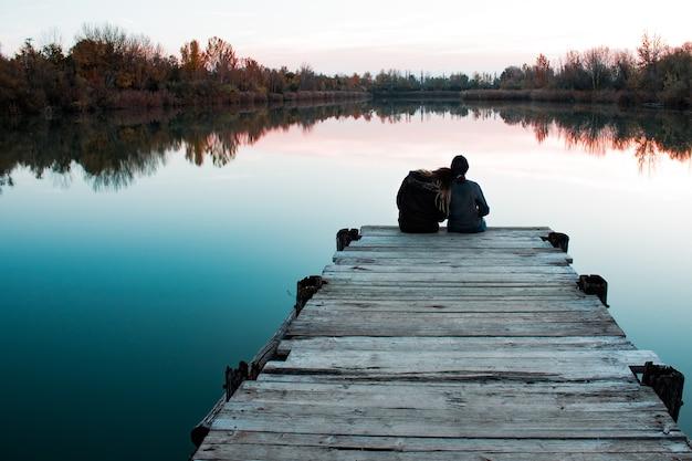 Amigos sentados em um cais de madeira com um deles descansando a cabeça no ombro perto do mar