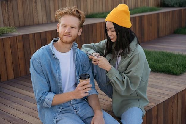 Amigos sentados juntos no parque, usando o celular, segurando uma xícara de café