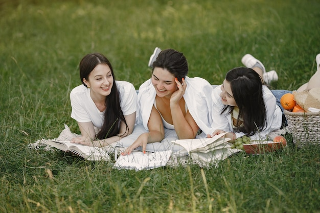 Amigos sentados na grama. meninas em um cobertor. mulher em uma camisa branca.