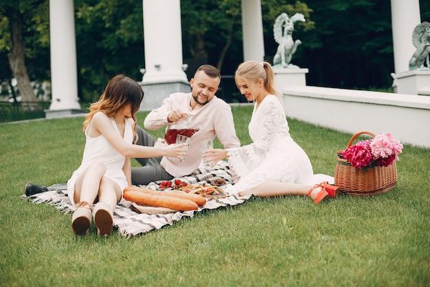 Amigos, sentando, em, um, jardim, ligado, um, piquenique