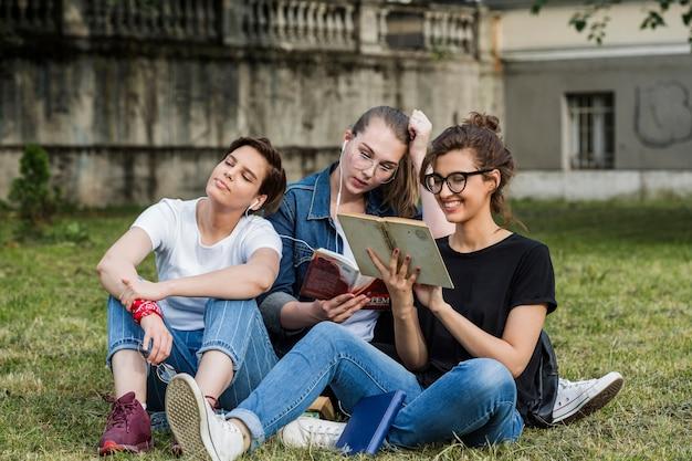 Amigos, sentando, parque, profundo, leitura