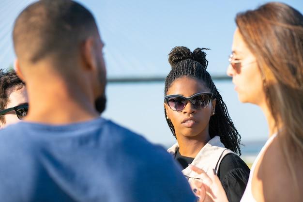 Amigos sérios conversando no parque durante o dia de sol. amigos focados a passar tempo juntos. lazer