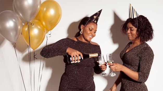 Amigos servindo taças de champanhe na festa de feliz aniversário