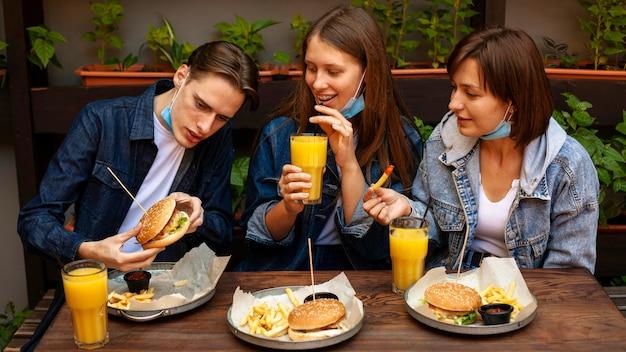 Amigos sorridentes a comer hambúrgueres com batatas fritas