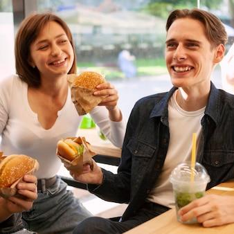 Amigos sorridentes a comer hambúrgueres