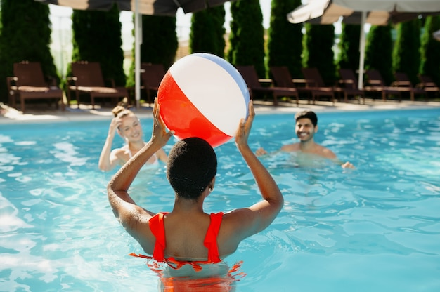 Amigos sorridentes brincando com bola na piscina