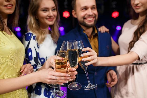 Amigos sorridentes com copos de champanhe no clube