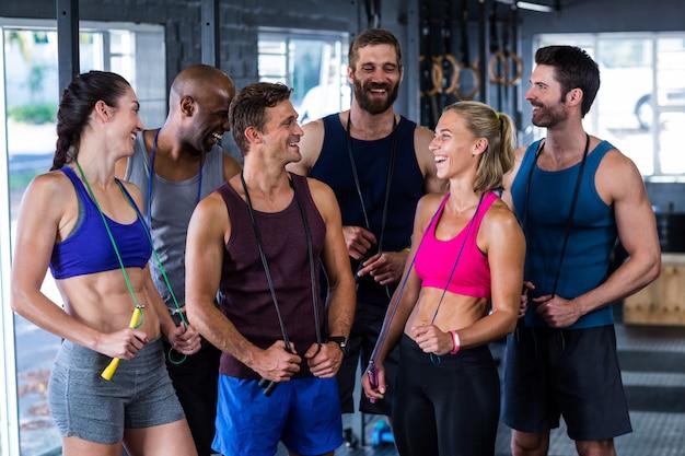 Amigos sorridentes com cordas de pular no ginásio