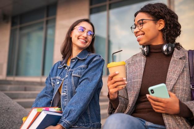 Amigos sorridentes com livros tomando café juntos ao ar livre