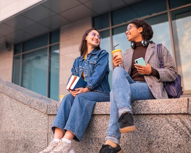 Amigos sorridentes com livros tomando café juntos