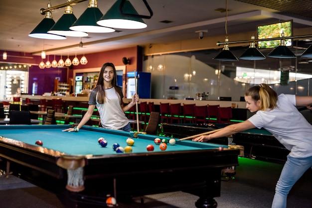Amigos sorridentes com tacos jogando bilhar em um bar