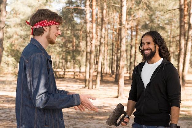 Amigos sorridentes conversando ao ar livre durante um churrasco