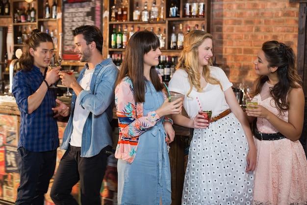 Amigos sorridentes conversando enquanto seguram bebidas