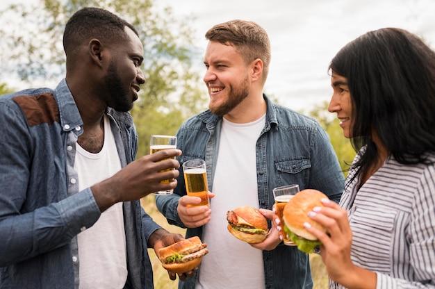 Amigos sorridentes de tiro médio com comida