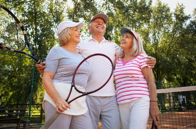 Amigos sorridentes de tiro médio com raquete