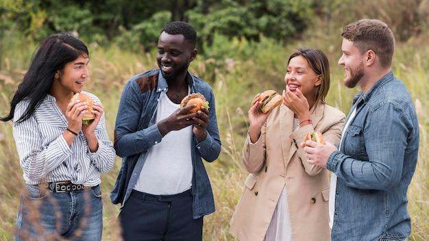 Amigos sorridentes de tiro médio comendo hambúrgueres
